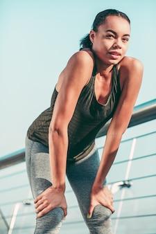 Calma mujer atlética en ropa deportiva de pie al aire libre con las manos en las piernas