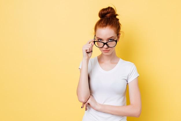 Calma mujer jengibre en anteojos mirando a través de anteojos a la cámara