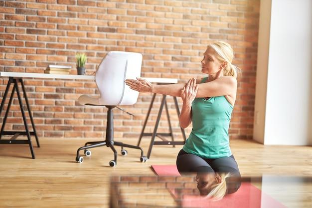Calma mujer rubia madura en ropa deportiva sentada en el suelo estirando sus brazos mientras practica