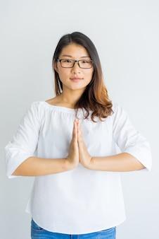Calma profesor de yoga haciendo gesto de namaste para saludar.