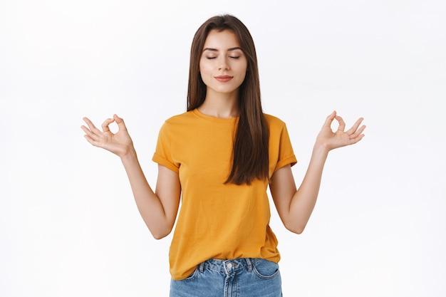 Calma, relajada y guapa morena libera el estrés, cierra los ojos y sonríe pacíficamente meditando con las manos extendidas hacia los lados en mudra, zen, postura de loto de pie, practica yoga, fondo blanco.
