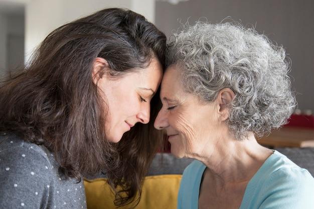 Calma senior madre e hija apoyándose mutuamente