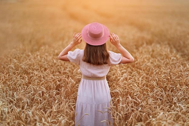 Calma serena mujer joven libre con sombrero y vestido de pie solo en el campo de trigo seco amarillo dorado y disfrutando de la hermosa vida del momento de libertad