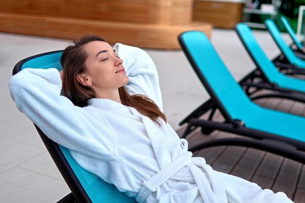 Calma serena mujer vestida con bata de baño con los ojos cerrados y las manos detrás de la cabeza relajándose y acostado en una tumbona en el balneario de bienestar. satisfacción, bienestar y tiempo de recreación. estilo de vida fácil