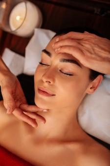 Calmado y relajado. atractiva clienta impecable que participa en un masaje meditativo con velas perfumadas