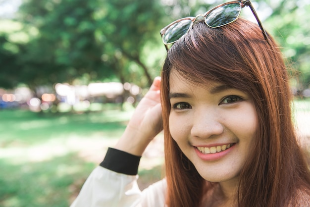 Calme a la mujer joven sonriente hermosa con la cola de caballo que disfruta del aire fresco al aire libre, relajándose con los ojos cerrados, sintiéndose vivo, respirando, soñando. copie el espacio, fondo verde de la naturaleza del parque. retrato de vista lateral
