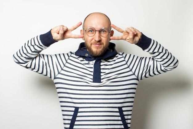 Calvo joven con barba, un suéter con capucha y gafas hace un gesto paz, hola en un blanco aislado.