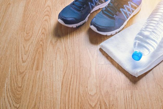 Calzado deportivo, agua, toalla sobre madera.