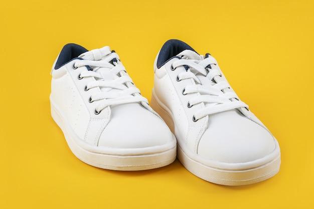 Calzado deportivo blanco, zapatillas de deporte con cordones sobre un fondo amarillo. concepto de estilo de vida deportivo vista superior endecha plana