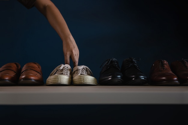 Calzado hombre moda. hombre recogiendo una zapatilla de deporte para usar. renunciar a un trabajo o ser concepto de relajación equilibrada