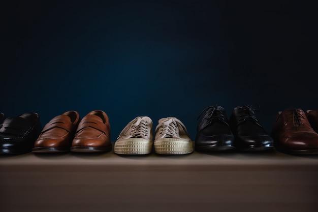 Calzado hombre moda. variedad de zapatos masculinos en el estante de la casa. incluye zapatillas, punta de ala, holgazán y oxford