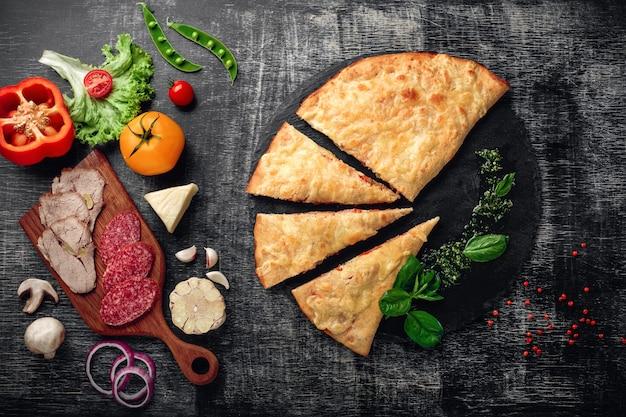 Calzone italiano tradicional de la pizza con los ingredientes en un fondo rasguñado de piedra y de madera oscuro