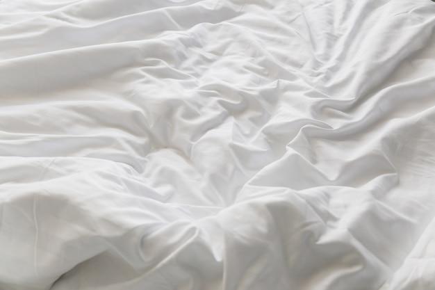 Cama arrugada deshecha con almohadas desordenadas blancas en la luz interior de la mañana del dormitorio
