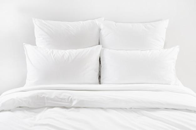 Cama blanca aislada, cuatro almohadas blancas y edredón sobre una cama.