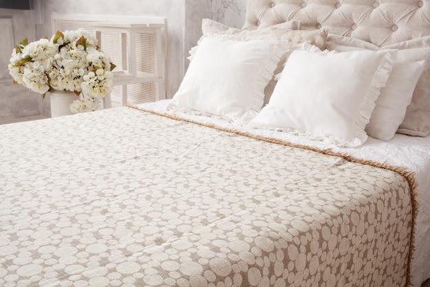 Cama blanca con colcha y almohadas.