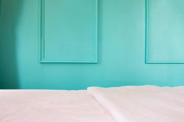Cama blanca en fondo azul de la pared en dormitorio.