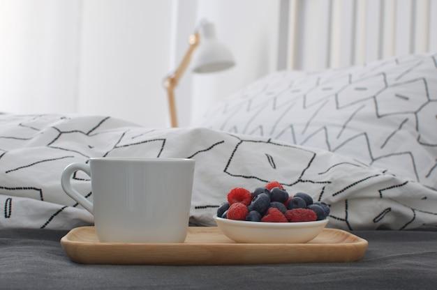 Cama de desayuno bandeja de madera interior temprano en la mañana espacio de copia sábana geométrica y funda de almohada bayas capuchino galletas