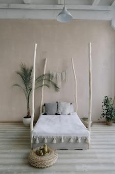 Cama de diseño de interiores de dormitorio exótico con dosel de madera y almohadas, manta de palmeras tropicales