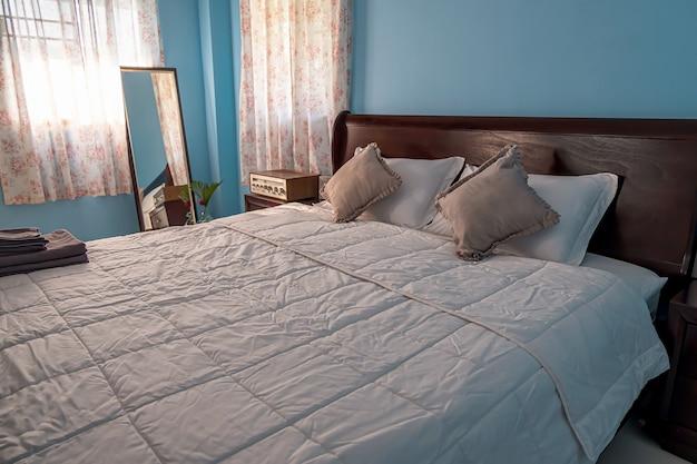 Cama doble de madera de estilo rústico en el dormitorio en la mañana de verano