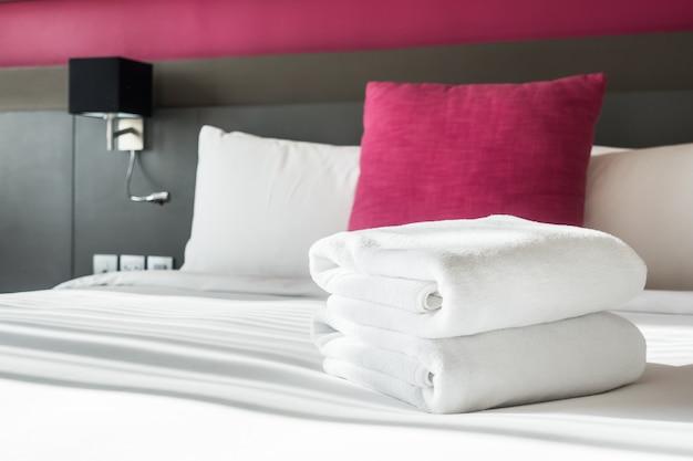 Cama con dos toallas blancas y un cojín