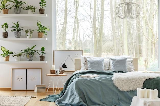 Cama king-size y plantas en estantes en el acogedor interior del dormitorio con una ventana grande