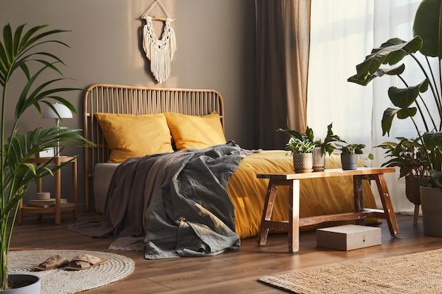 Cama de madera en el elegante interior del dormitorio neutro con muebles de diseño, decoración, alfombra, banco, plantas tropicales, sábanas, mantas, almohadas y elegantes accesorios personales en la decoración del hogar.
