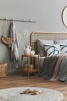 Cama de madera en el interior del dormitorio neutro con estilo con muebles de diseño, decoración, alfombra, banco, flores secas en jarrón, sábanas, mantas, almohadas y elegantes accesorios personales en la decoración del hogar.