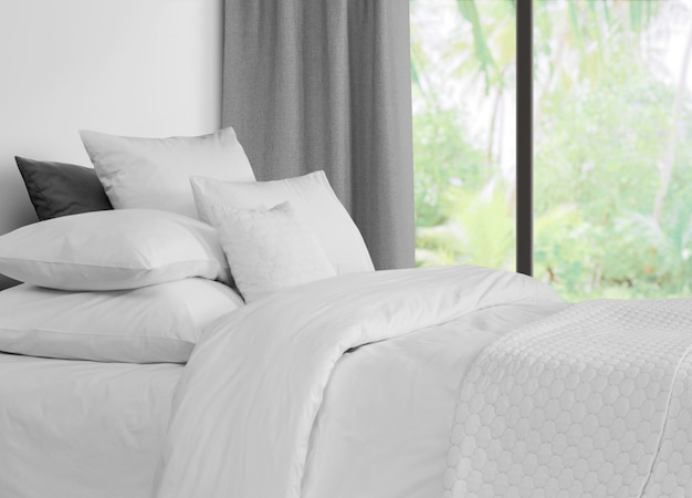Cama con ropa de cama contra una ventana con cortinas grises.