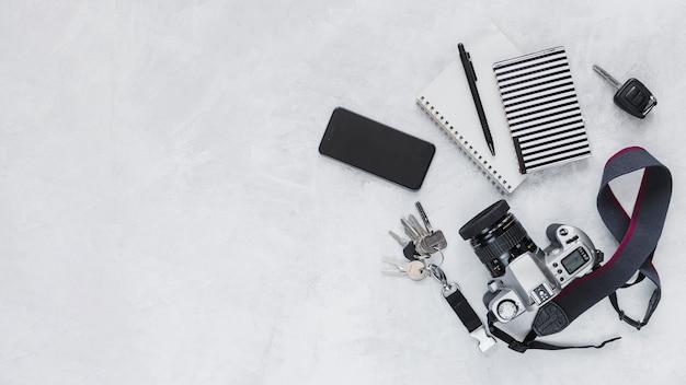 Cámara de alta tecnología, teléfono celular, cuaderno y llaves en el fondo