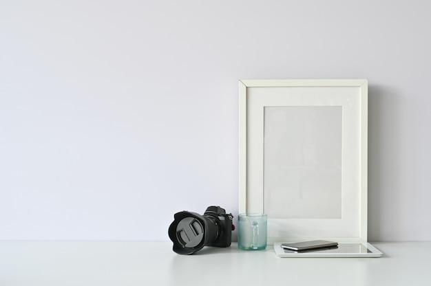 Cámara de área de trabajo, marco de fotos, vidrio, teléfono inteligente y tableta en mesa.