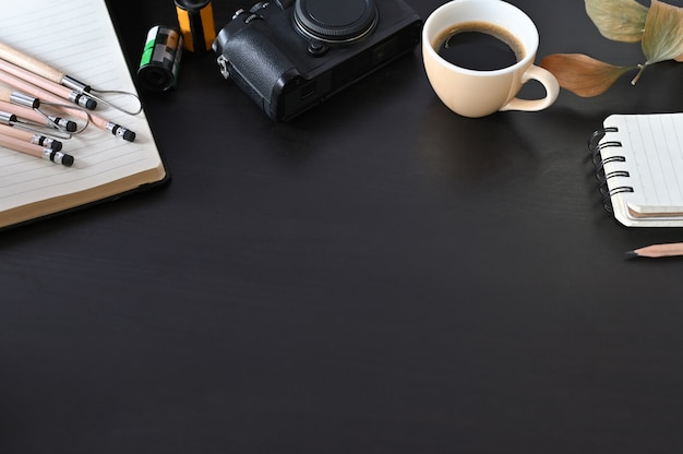 Cámara, café y documento de nota creativos del lugar de trabajo sobre la tabla negra con el foco selectivo.