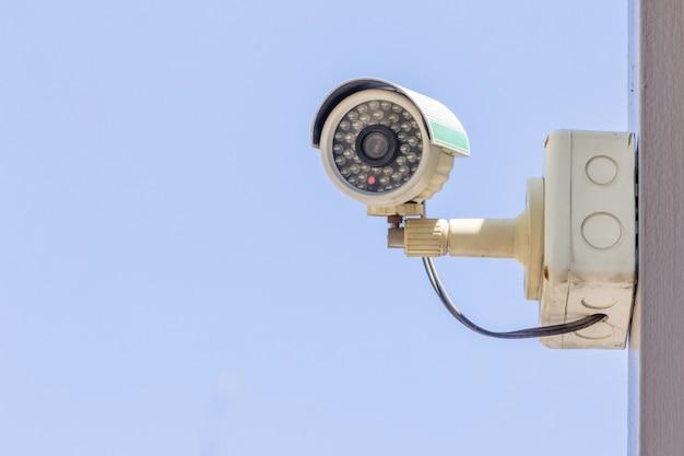 Cámara de cctv de seguridad o sistema de vigilancia en un edificio de oficinas sobre fondo de cielo azul