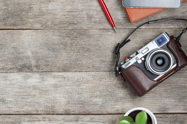 Cámara clásica, con libreta marrón, bolígrafo rojo, teléfono y crecimiento verde. lista conceptual para un fotógrafo de viajes.