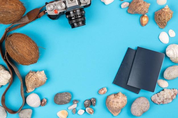 Cámara, cocos, conchas y documentos sobre un fondo azul. antecedentes para el viajero.