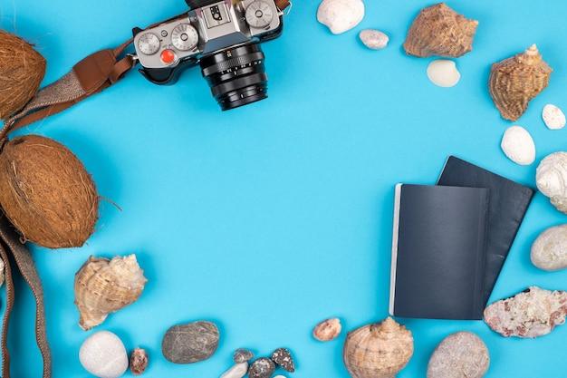 Cámara, cocos, conchas y documentos sobre un fondo azul.fondo para el viajero
