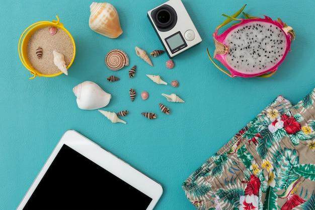 Cámara, concha marina, arena, pantalones de playa, fruta del dragón y teléfono inteligente sobre azul