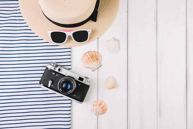 Cámara y conchas marinas cerca de sombrero y gafas de sol