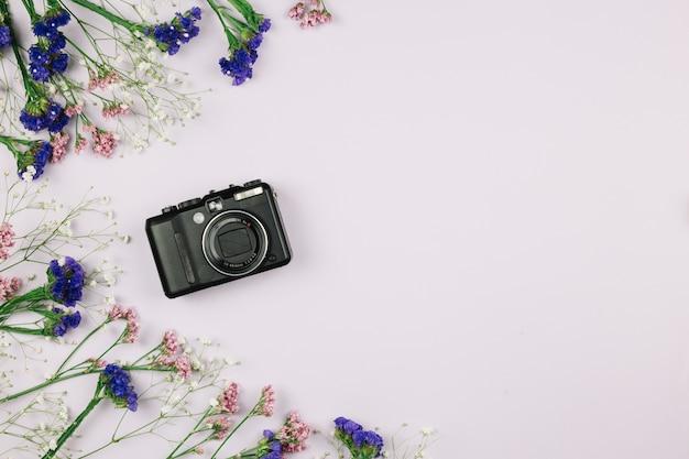 Cámara digital con decoración floral sobre fondo blanco.