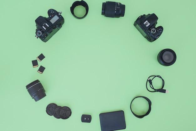Cámara digital profesional y accesorios dispuestos sobre fondo verde.