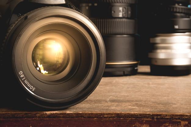 Cámara dslr negra con lente de primera calidad de 50 mm y 1.8g sobre una superficie de caja vintage de madera marrón