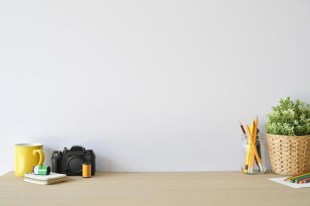 Cámara del espacio de trabajo y materiales de oficina creativos en el escritorio de madera con el espacio de la copia.