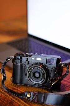 Cámara de fotos en un estuche de cuero negro, sobre una mesa de madera oscura. al lado de la computadora portátil. lugar de trabajo y accesorios del fotógrafo o un profesional independiente