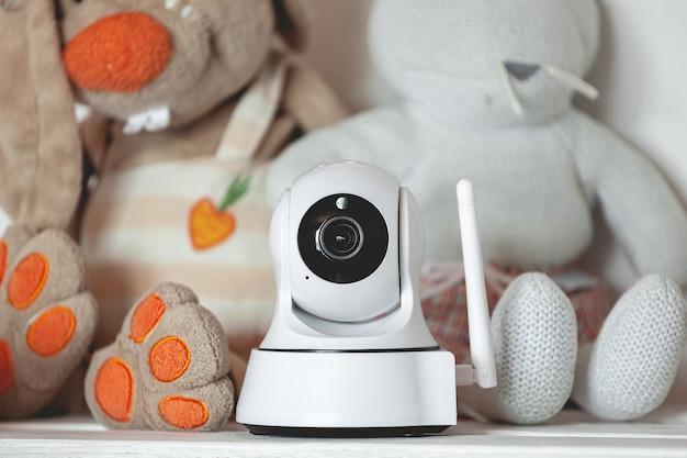 Cámara ip en el estante con juguetes, que sirve como monitor para bebés.