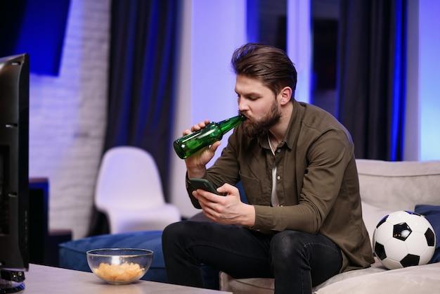 Cámara lenta de un guapo hombre moderno de 30 años con barba que se sienta frente a la televisión y mira periódicamente partidos de fútbol y aplicaciones en su móvil mientras bebe cerveza