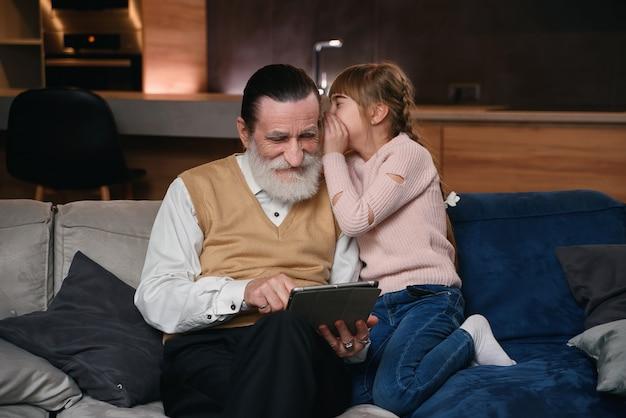 Cámara lenta de una linda y alegre niña de 12 años con coletas divertidas que susurra al oído del abuelo su secreto mientras se sientan juntas en el sofá de casa.