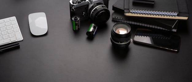 Cámara con lente y smartphone en una mesa negra