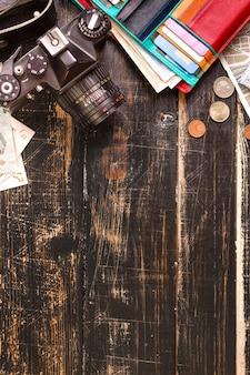 Cámara, mapas turísticos, auriculares, billetera con tarjetas de crédito, billetes y monedas en el escritorio negro.