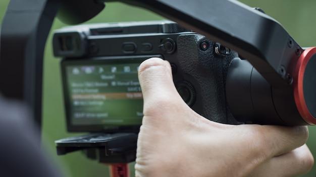 Cámara de menú de ajuste de video o espejo digital profesional en el trípode para grabar tomando fotos