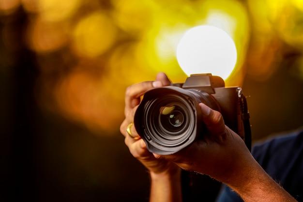 Cámara negra sostenida por la mano del fotógrafo con puesta de sol