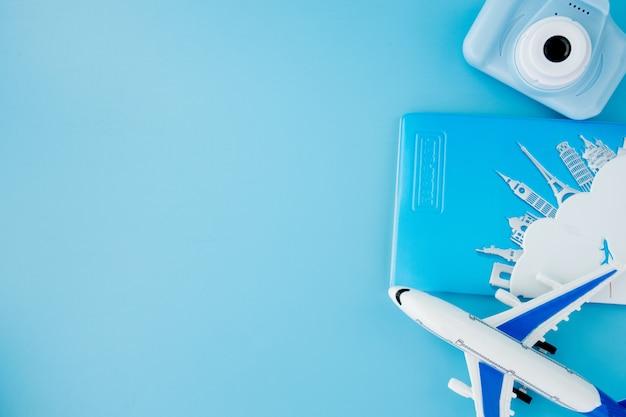 Cámara, pasaporte y avión en superficie azul claro